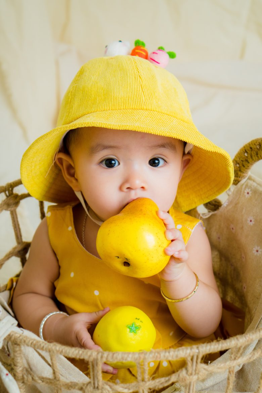 Imagen de un bebé en una cesta comiendo fruta por el método baby-led weaning