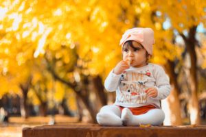 Imagen en la que aparee un bebé comiendo un trozo de pollo