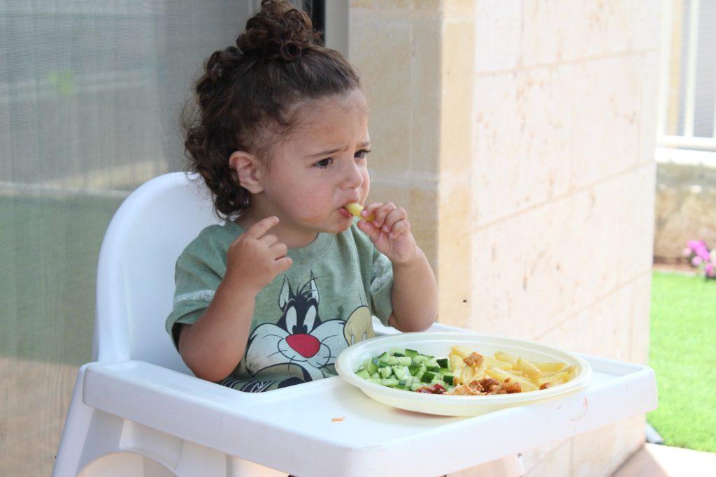 Niña sentada en su trona comiendo sola gracias al baby-led weaning