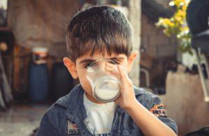 la imagen muestra un niño bebiendo un vaso de leche de vaca entera