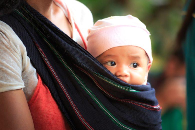 bebé siendo porteado con un fular tejido
